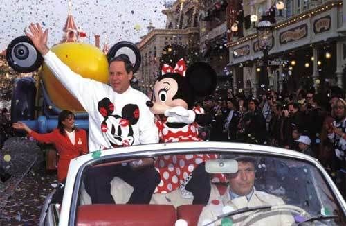 Michael Eisner rides along with Minnie Mouse in the opening day parade at Euro Disneyland Park.
