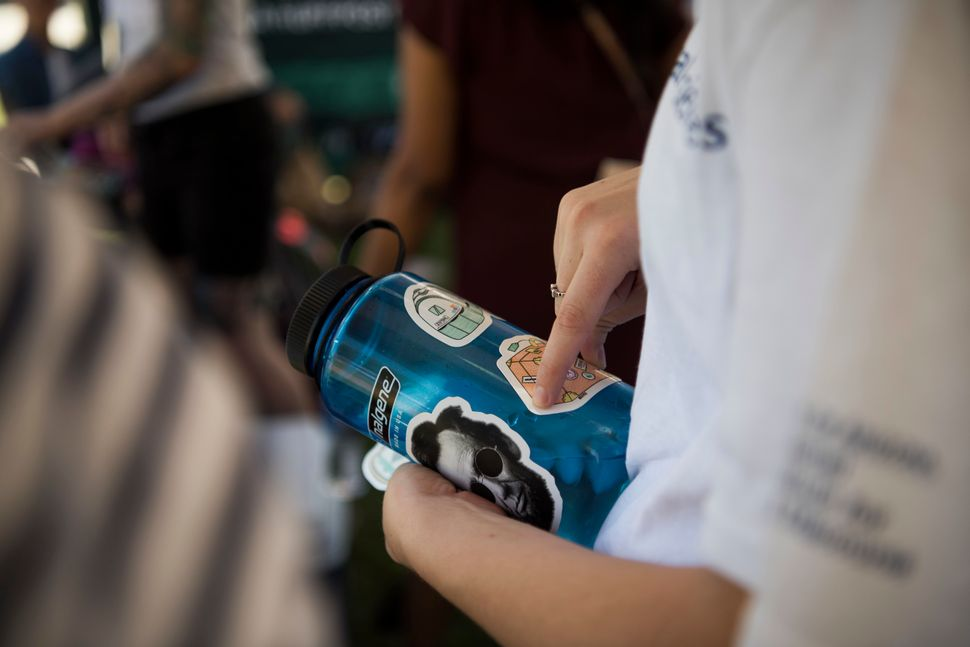 A student puts stickers on a water bottle during HuffPost's visit to University of Arizona.