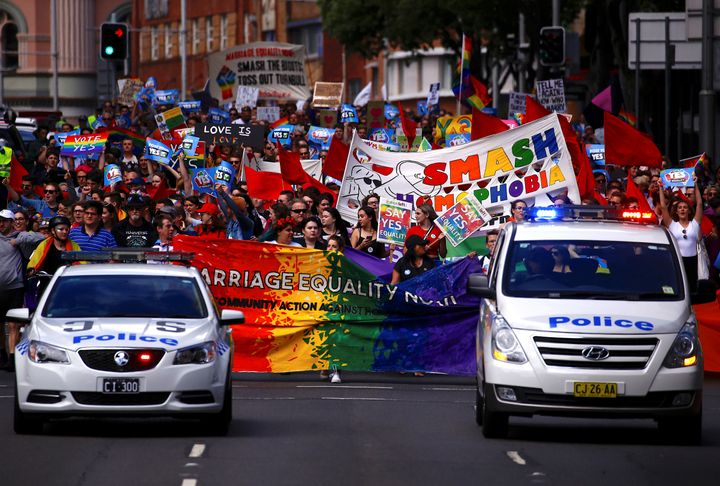 Police drive in front of marchers holding signs and banners as they participate in a marriage equality march in Sydney.