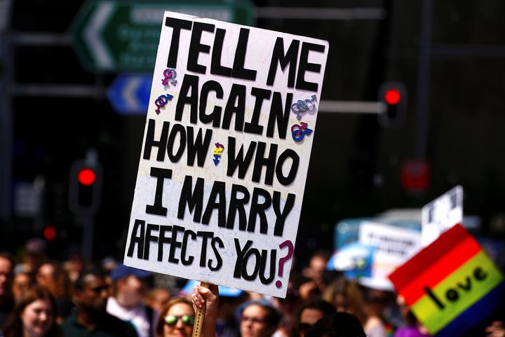 A marcher holds aloft a sign as they participate in a marriage equality march in central Sydney.
