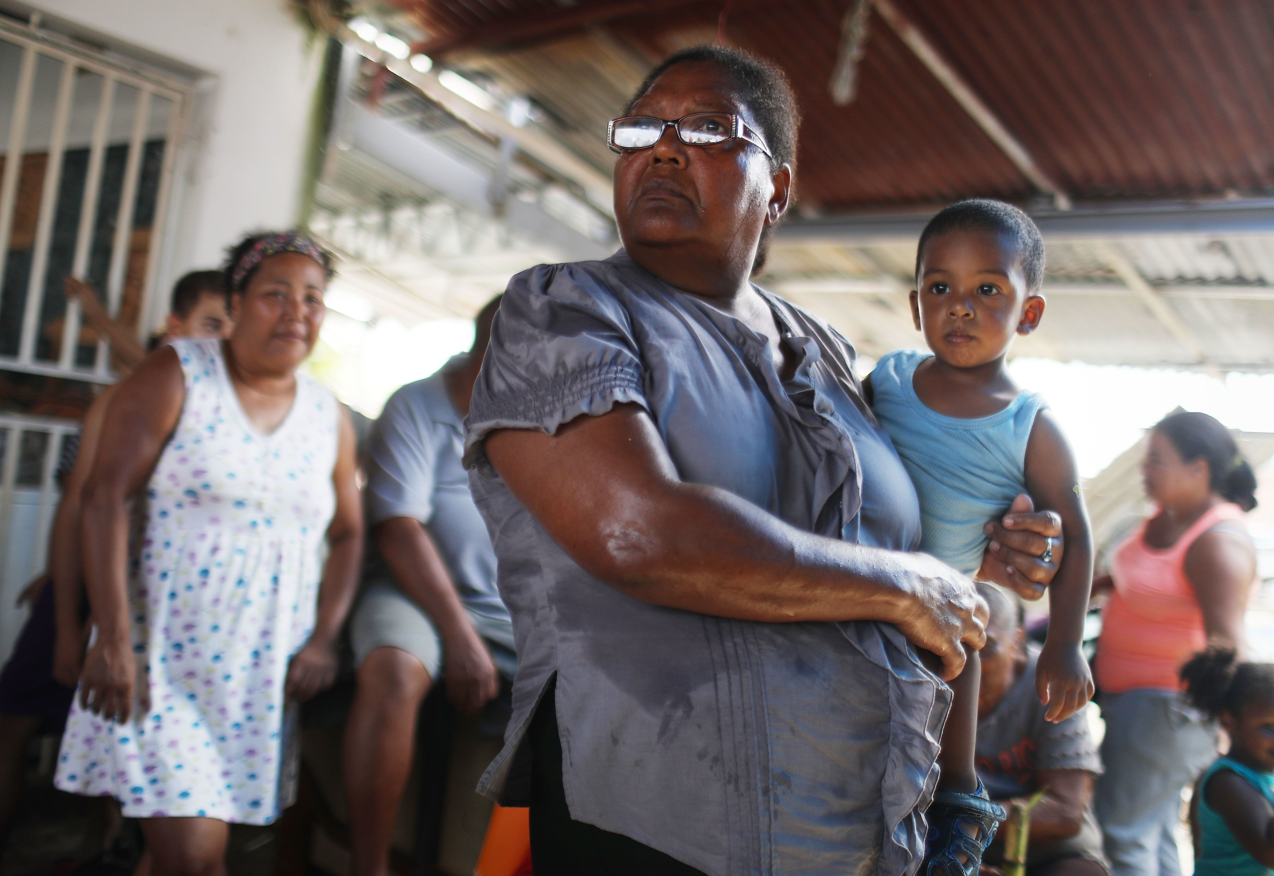 SAN ISIDRO, PUERTO RICO - OCTOBER 17:  Residents wait in the shade for food and water aid, provided by FEMA, to arrive in a neighborhood without grid electricity or running water on October 17, 2017 in San Isidro, Puerto Rico. The food and water delivery mission included U.S. Army, U.S. Coast Guard and Puerto Rico Hacienda forces. Residents said this was the first official governmental delivery of food and water to the community, nearly four weeks after the hurricane hit. Puerto Rico is suffering shortages of food and water in areas and only 17.7 percent of grid electricity has been restored. Puerto Rico experienced widespread damage including most of the electrical, gas and water grid as well as agriculture after Hurricane Maria, a category 4 hurricane, swept through.  (Photo by Mario Tama/Getty Images)