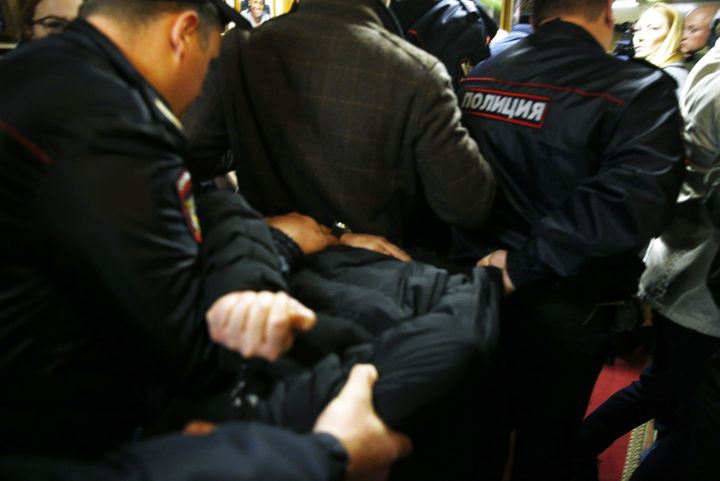 Police officers detain the man who attacked Tatyana Felgenhauer, a radio journalist at the Ekho Moskvy radio station in