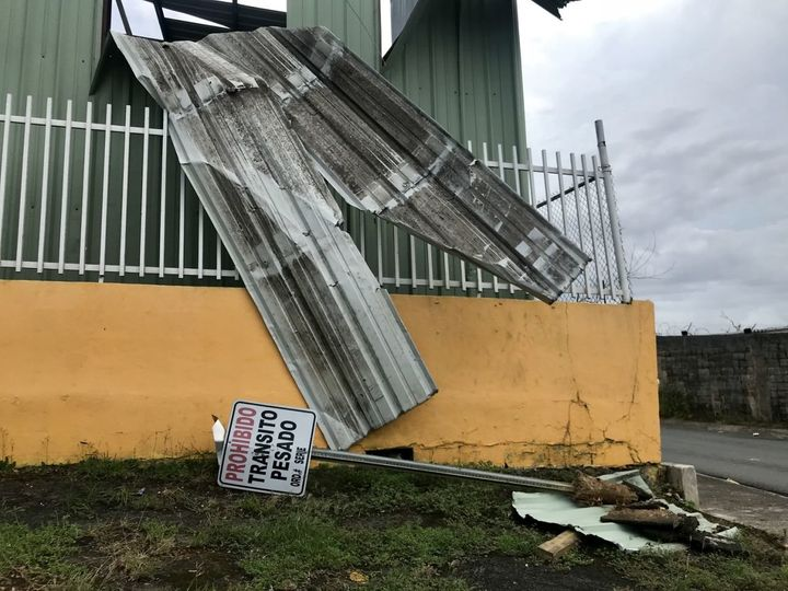 A downed no trespassing sign lays on the grass in front of a building damaged by Hurricane Maria in Bayamon, Puerto Rico.