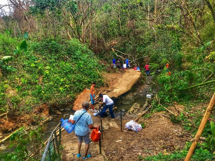 People bathe in and collect water from a stream in Bayamon, Puerto Rico.