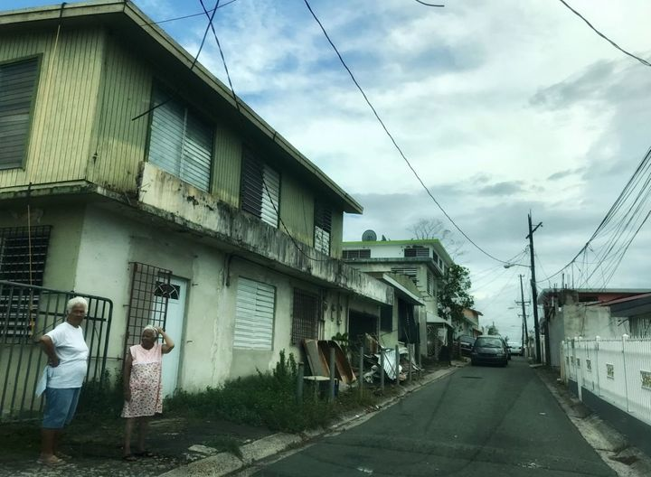 Two women stand on a residential street in Bayamon, Puerto Rico on Oct. 7, 2017 Nearly three weeks after Hurricane Maria stru