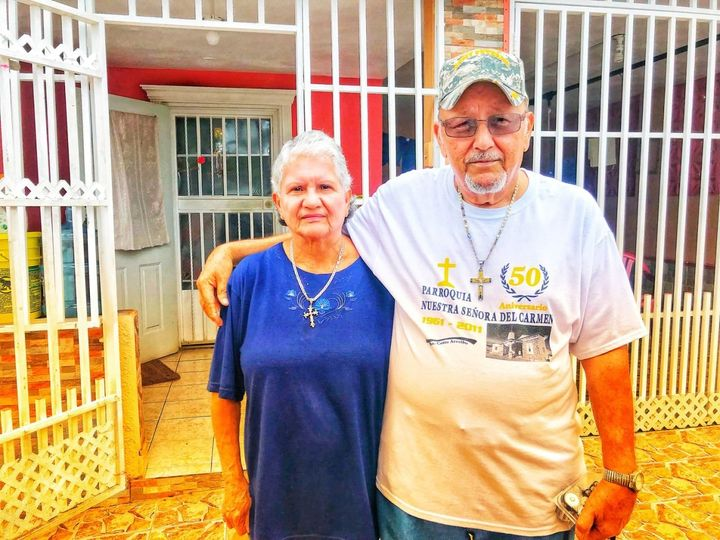 Ramona and Santos Lopez Caraballo stand outside their home in Arecibo, Puerto Rico on Oct. 10, 2017. The couple had no cell s
