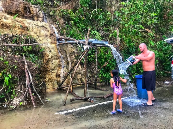A young girl and her father rinse off in naturally flowing water from the side of a mountain in Ciales, Puerto Rico on Oct. 1
