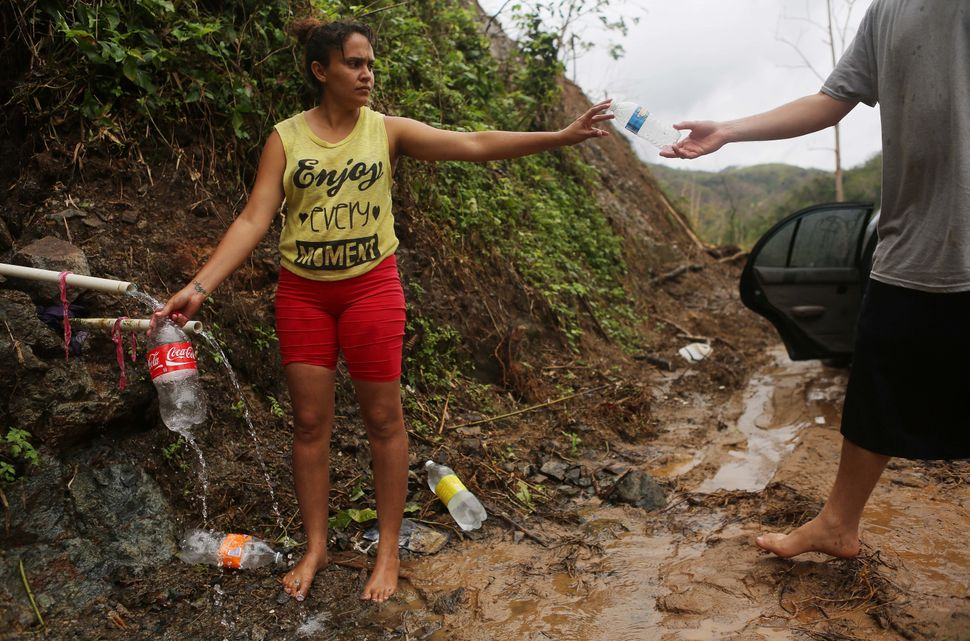 Yanira Rios collects spring water nearly three weeks after Hurricane Maria destroyed her town of Utuado. It's not clear if th