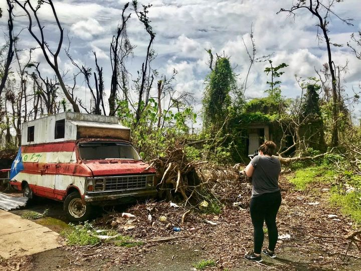 Megan Vazquez photographs the destruction around an abandoned van and hot dog stand near her hometown of Bayamon, Puerto Rico
