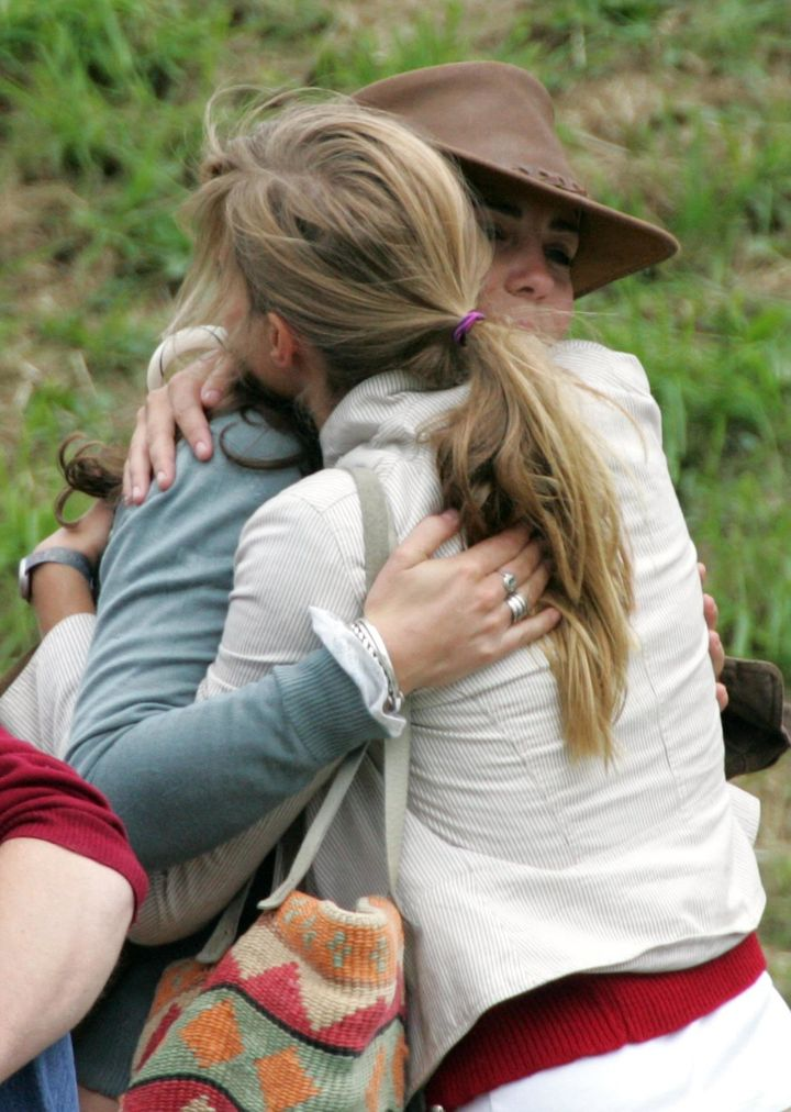 Kate Middleton, then-girlfriend of Prince William, hugs a friend on the second day of the Gatcombe Park Festival on August 6,