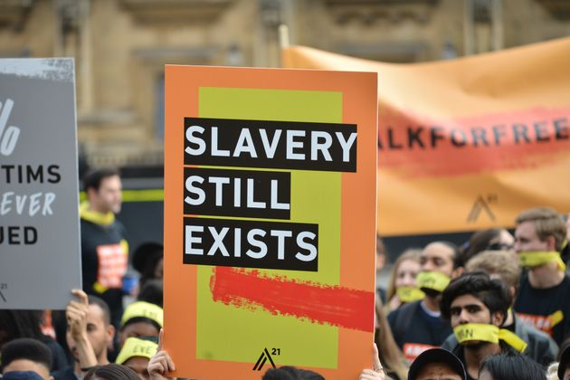 People marching against modern slavery through London wearing face masks representing the silence of...