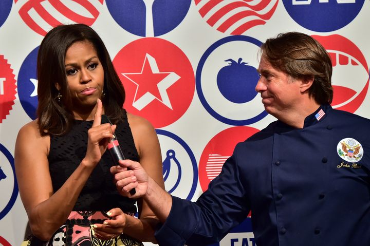 Michelle Obama speaks next to chef John Besh at the James Beard American Restaurant during a visit in Milan on June 17, 2015.