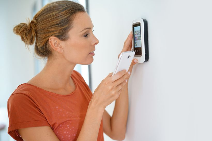 Woman operating smart home device and phone simultaneously.