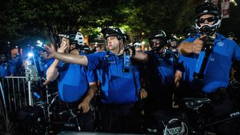 Police in St Louis aim tear gas canisters at a crowd last month