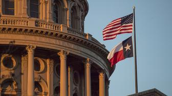 An American flag flies with the Texas state flag outside the Texas State Capitol building in Austin, Texas, U.S., on Tuesday, March 14, 2017. Austin has spent the last 10 monthsengaged ina bigexperimentin urban transportation.Several hundreds of thousands of people will descend upon Austin for the annual South by Southwest festival, a nine-day event that could be described as a tech conference, a music and film festival. Photographer: David Paul Morris/Bloomberg via Getty Images