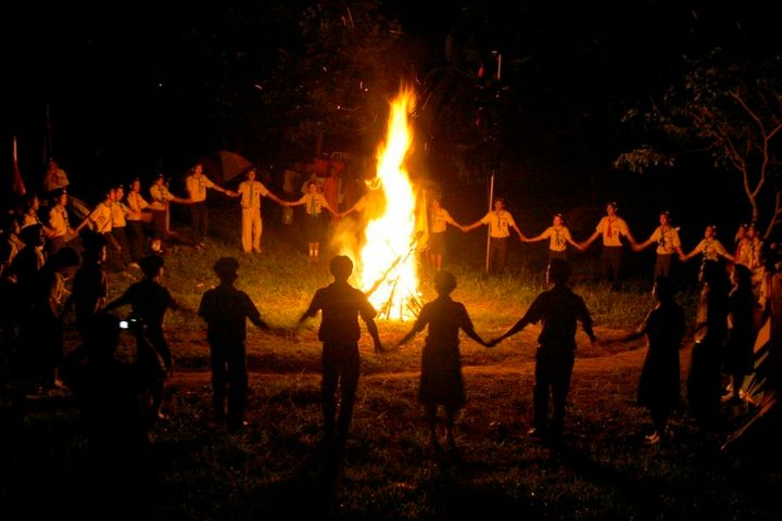 Cambodian boy and girl scouts join hands as they dance around a bonfire in 2008.
