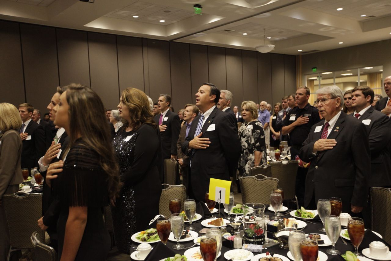 Attendees of Roy Moore's gala event hold their hands over their hearts for the Pledge of Allegiance.