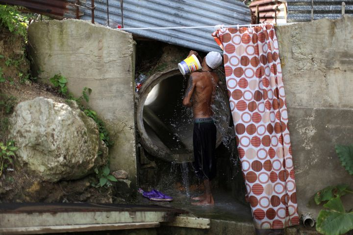 Israel Ayala takes a bath with water coming through a pipe on Oct. 19, 2017, after Puerto Rico was hit by Hurr