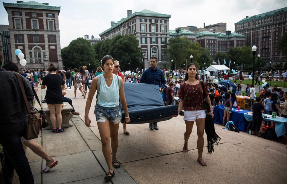 Emma Sulkowicz carries a mattress, with the help of three strangers who met her moments before, in protest...