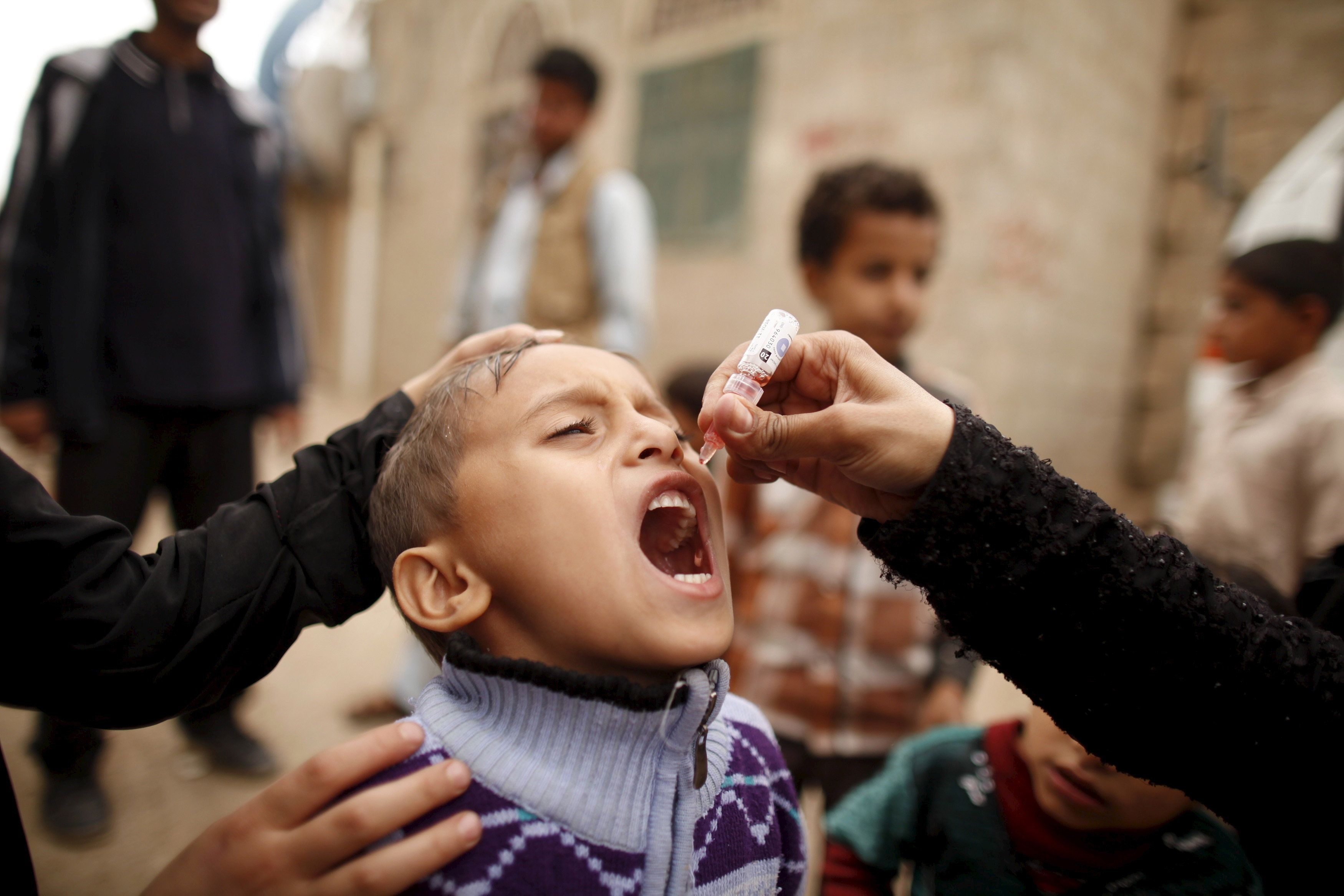 A boy receives polio vaccination drops during a house-to-house vaccination campaign in Yemen's capital, Sanaa, on April 10, 2