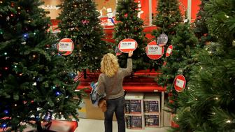 UNITED STATES - NOVEMBER 08:  Patti Bowden inspects an artificial Christmas tree as she shops at a Target store in Raleigh, North Carolina, on Saturday, Nov. 17, 2007. Target Corp. is expected to releases its quarterly results on Tuesday, Nov. 20, 2007.  (Photo by Jim R. Bounds/Bloomberg via Getty Images)