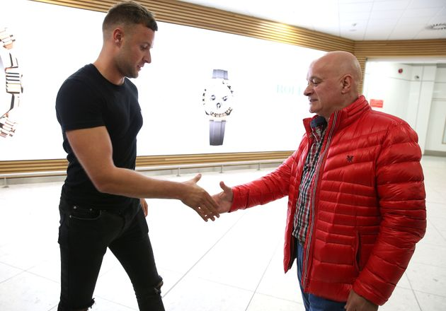Jamie Harron with his father Graham after arriving at Glasgow