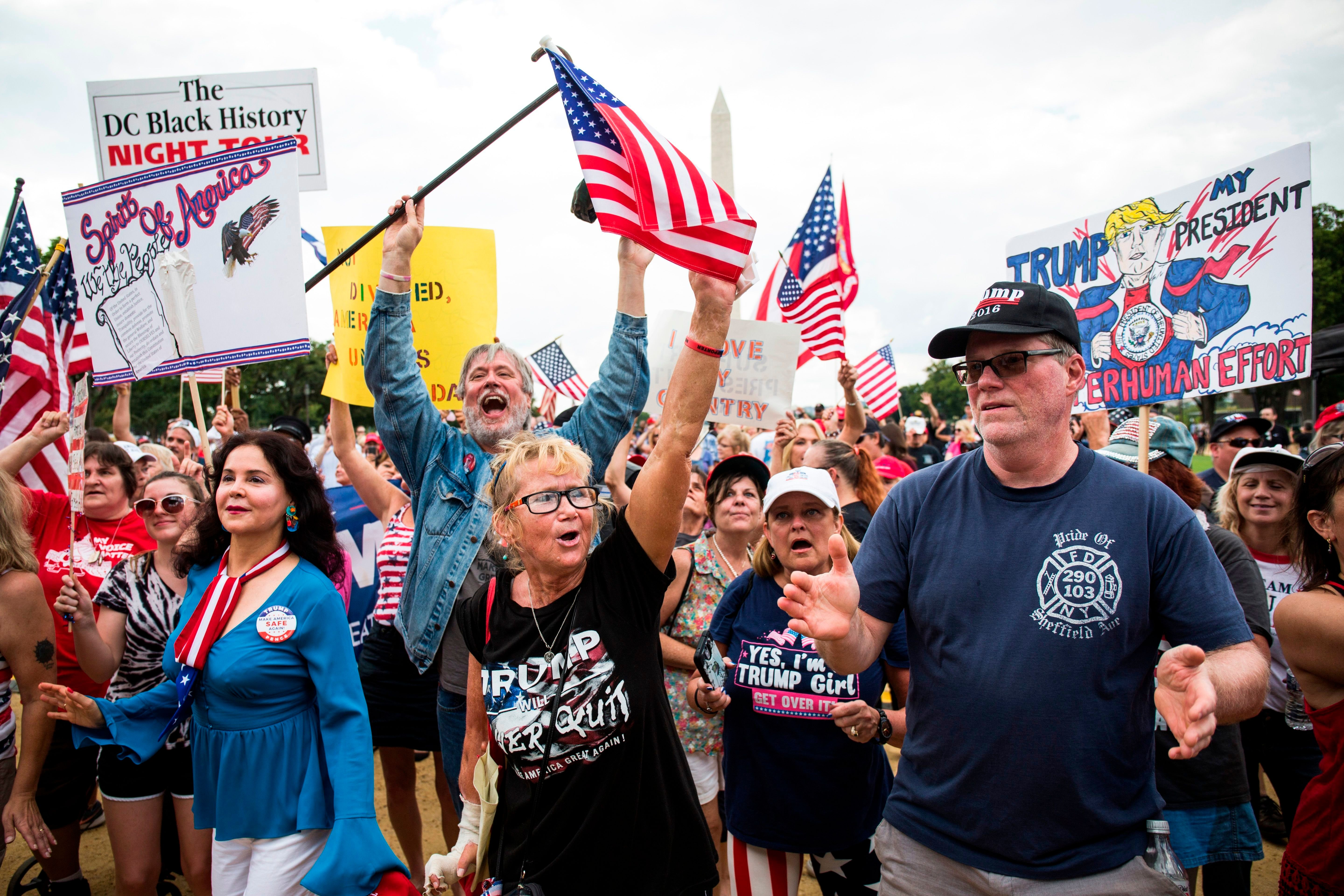 Demonstrators wave national flags and placards during the pro-Trump 'Mother of All Rallies' on the National Mall in Washington, DC on September 16, 2017.   Supporters of President Donald Trump gathered in the US capital to show support of 'free-speech' dubbed the Mother of All Rallies. / AFP PHOTO / ZACH GIBSON        (Photo credit should read ZACH GIBSON/AFP/Getty Images)