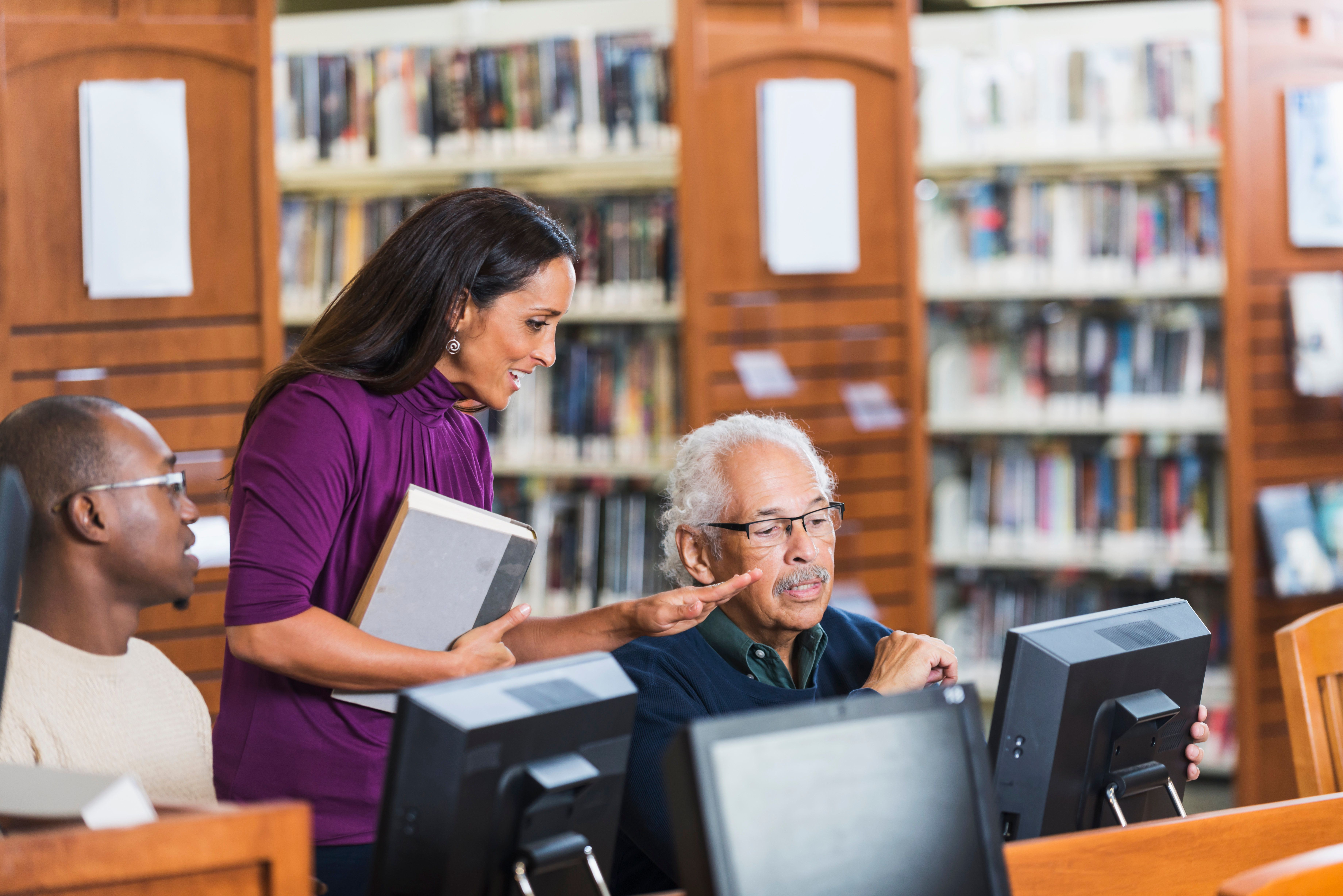 Senior Hispanic man in his late 70s using a computer in the library, getting help from a female librarian.  He is sitting down, looking at the screen.  She is standing beside him, talking and gesturing with her hand.  A young African American man is watching and listening to their conversation.