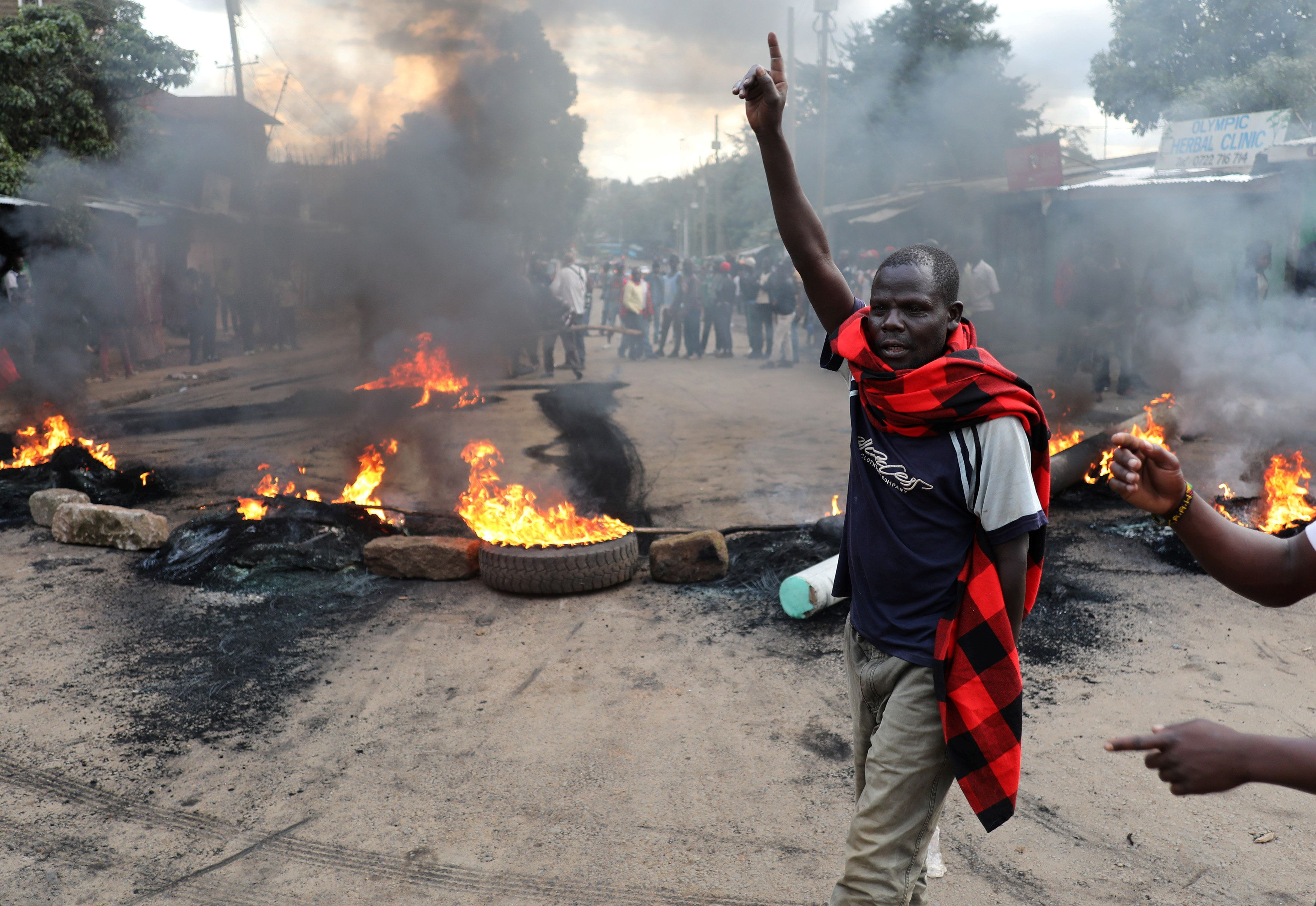 An opposition supporter gestures in front of a burned barricade in Kibera slum in Nairobi, Kenya October 25, 2017.