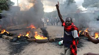 An opposition supporter gestures in front of a burned barricade in Kibera slum in Nairobi, Kenya October 25, 2017. REUTERS/Goran Tomasevic