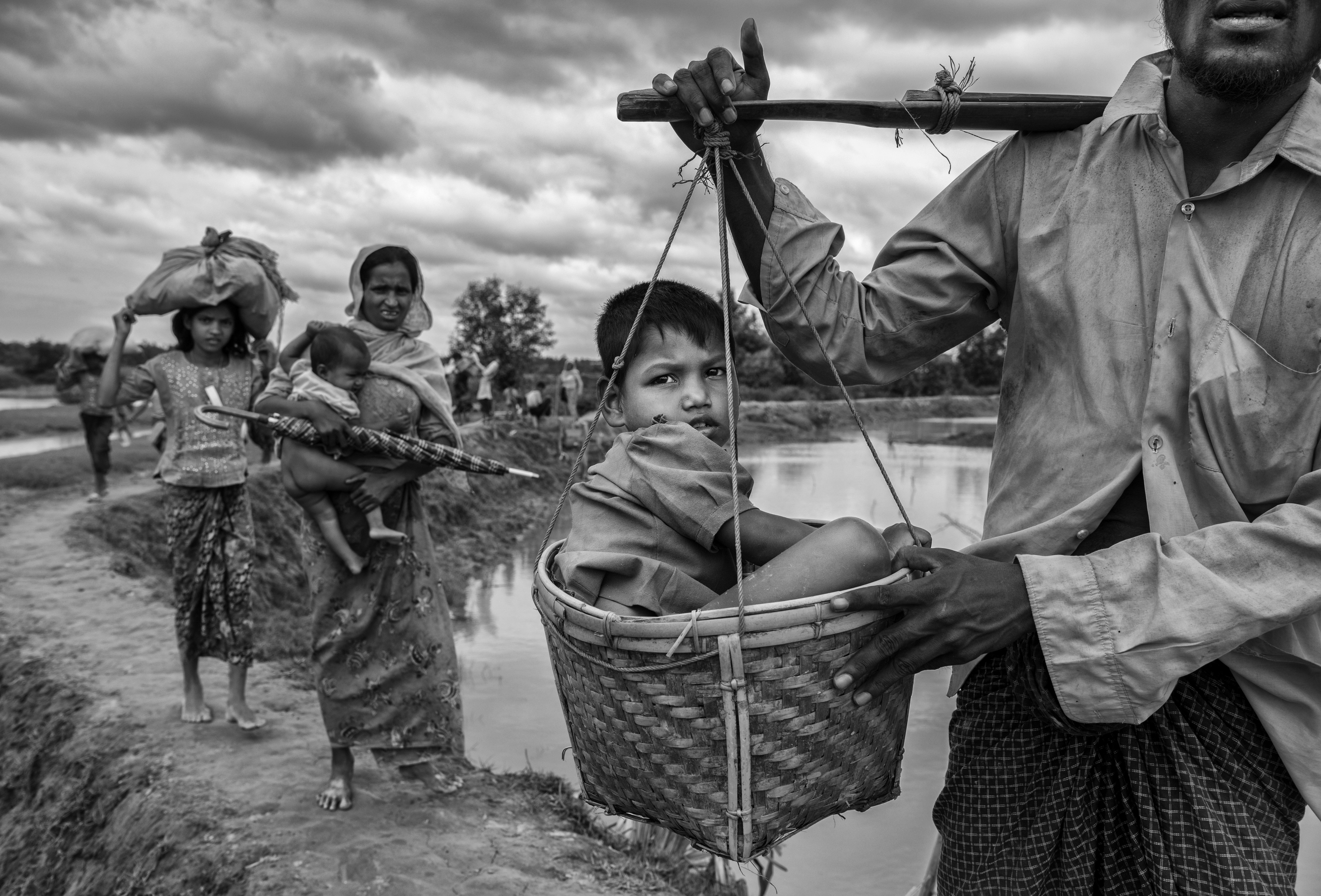 A Rohingya refugee boy is carried in a basket by a relative on Sept. 24 after crossing the border on...