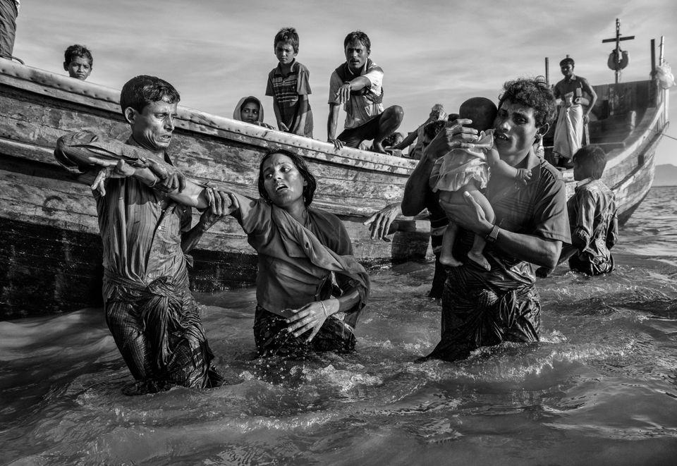 A Rohingya refugee woman is helped from a boat as she arrives exhausted on the Bangladesh side of the...
