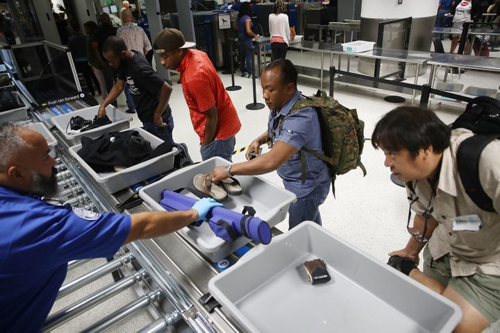 Travelers use automated screening lanes at Miami International Airport