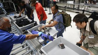 MIAMI, FL - OCTOBER 24:  Travelers use the automated screening lanes funded by American Airlines and installed by the Transportation Security Administration at Miami International Airport on October 24, 2017 in Miami, Florida. The automated checkpoint technology, which is now in use at 11 airports across the country, is said by officials with the Transportation Security Administration to enhance security efficiency as well as decrease the amount of time spent in the security screening process.  (Photo by Joe Raedle/Getty Images)
