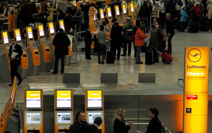 Passengers line up at a Lufthansa check-in counter at Frankfurt Airport