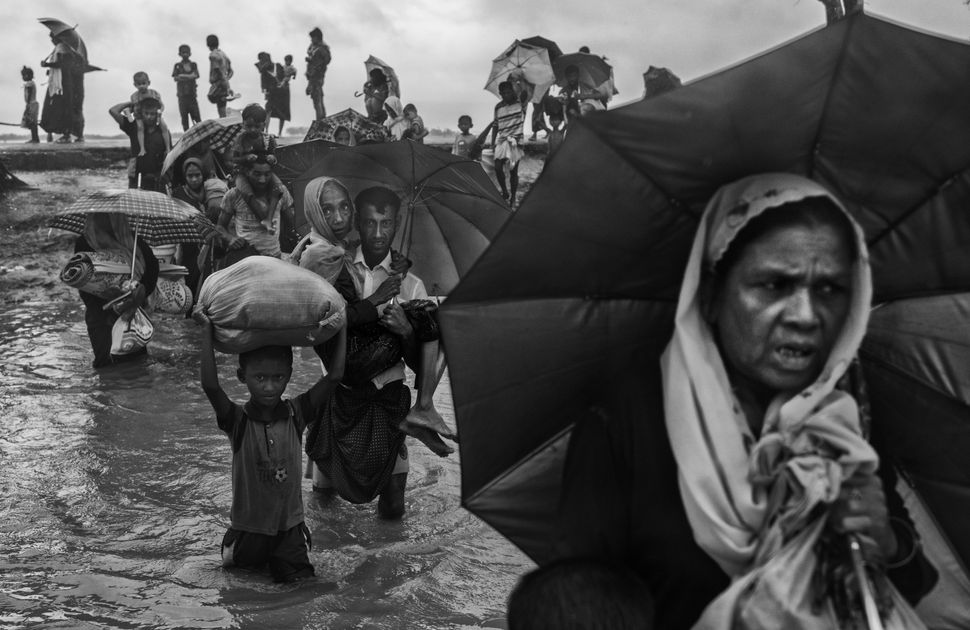 Rohingya refugees carry their belongings as they walk through water on the Bangladesh side of the Naf River after fleeing the