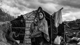 COX'S BAZAR, BANGLADESH - SEPTEMBER 27: A Rohingya refugee woman holds her child as she stands outside her shelter at the sprawling Balukali refugee camp on September 27, 2017 in Cox's Bazar, Bangladesh. More than half a million Rohingya refugees have flooded into Bangladesh to flee an offensive by Myanmar's military that the United Nations has called 'a textbook example of ethnic cleansing'.  The refugee population is expected to swell further, with thousands more Rohingya Muslims said to be making the perilous journey on foot toward the border, or paying smugglers to take them across by water in wooden boats. Hundreds are known to have died trying to escape, and survivors arrive with horrifying accounts of villages burned, women raped, and scores killed in the 'clearance operations' by Myanmar's army and Buddhist mobs that were sparked by militant attacks on security posts in Rakhine state on August 25, 2017.  What the Rohingya refugees flee to is a different kind of suffering in sprawling makeshift camps rife with fears of malnutrition, cholera, and other diseases.  Aid organizations are struggling to keep pace with the scale of need and the staggering number of them - an estimated 60 percent - who are children arriving alone. Bangladesh, whose acceptance of the refugees has been praised by humanitarian officials for saving lives, has urged the creation of an internationally-recognized 'safe zone' where refugees can return, though Rohingya Muslims have long been persecuted in predominantly Buddhist Myanmar. World leaders are still debating how to confront the country and its de facto leader, Aung San Suu Kyi, a Nobel Peace Prize laureate who championed democracy, but now appears unable or unwilling to stop the army's brutal crackdown.  (Photo by Kevin Frayer/Getty Images)