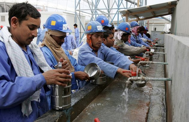 Workers of the Sport City tower wash their dishes after their lunch break in Doha, Qatar, Feb. 4,