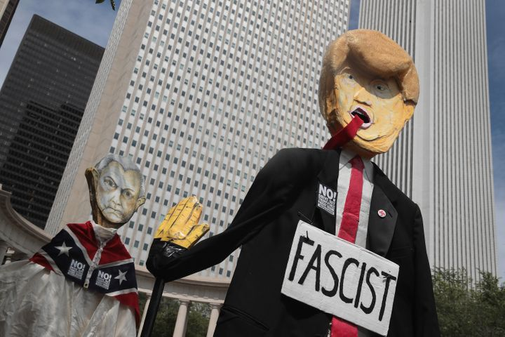 Demonstrators in Chicago protesting the alt-right and mourning Charlottesville, Virginia, victims carry puppets of President Donald Trump and U.S. Attorney General Jeff Sessionson Aug. 13.