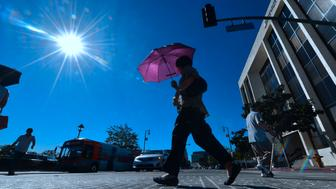 A pedestrian uses an umbrella on a hot sunny morning in Los Angeles October 24, 2017 amid a late season heatwave hitting southern California.   Record temperatures in some locations including downtown Los Angeles reached 37 degrees Celsius (99 degrees Fahrenheit) before noon, tying a record set in 1909.  / AFP PHOTO / FREDERIC J. BROWN        (Photo credit should read FREDERIC J. BROWN/AFP/Getty Images)