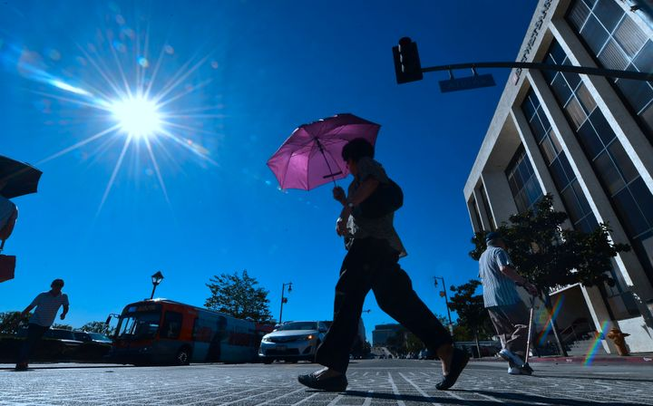 A pedestrian uses an umbrella as a heat shield in Los Angeles on Tuesday,when temperatures climbed past 100 downtown.