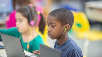 A multi-ethnic group of elementary age children are working on laptops and listening to music in the computer lab of their school.