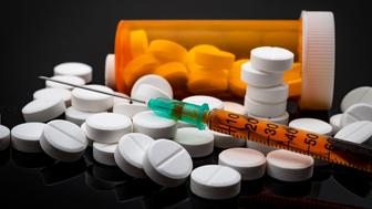 Opioid epidemic and drug abuse concept with a heroin syringe or other narcotic substances next to a bottle of prescription opioids. Oxycodone is the generic name for a range of opioid painkillers