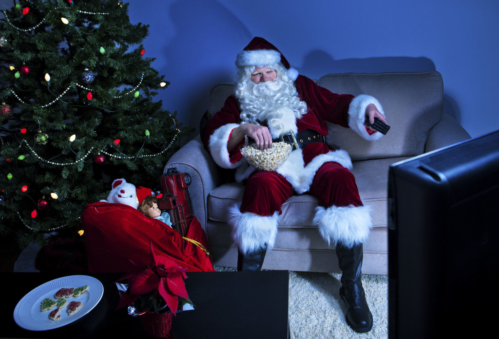 Santa Claus takes a break from delivering toys and watches some television.