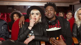 Multi ethnic group of people in the movie theater. Close up of afro american young man holding popcorn in hand, embracing his blonde girlfriend.