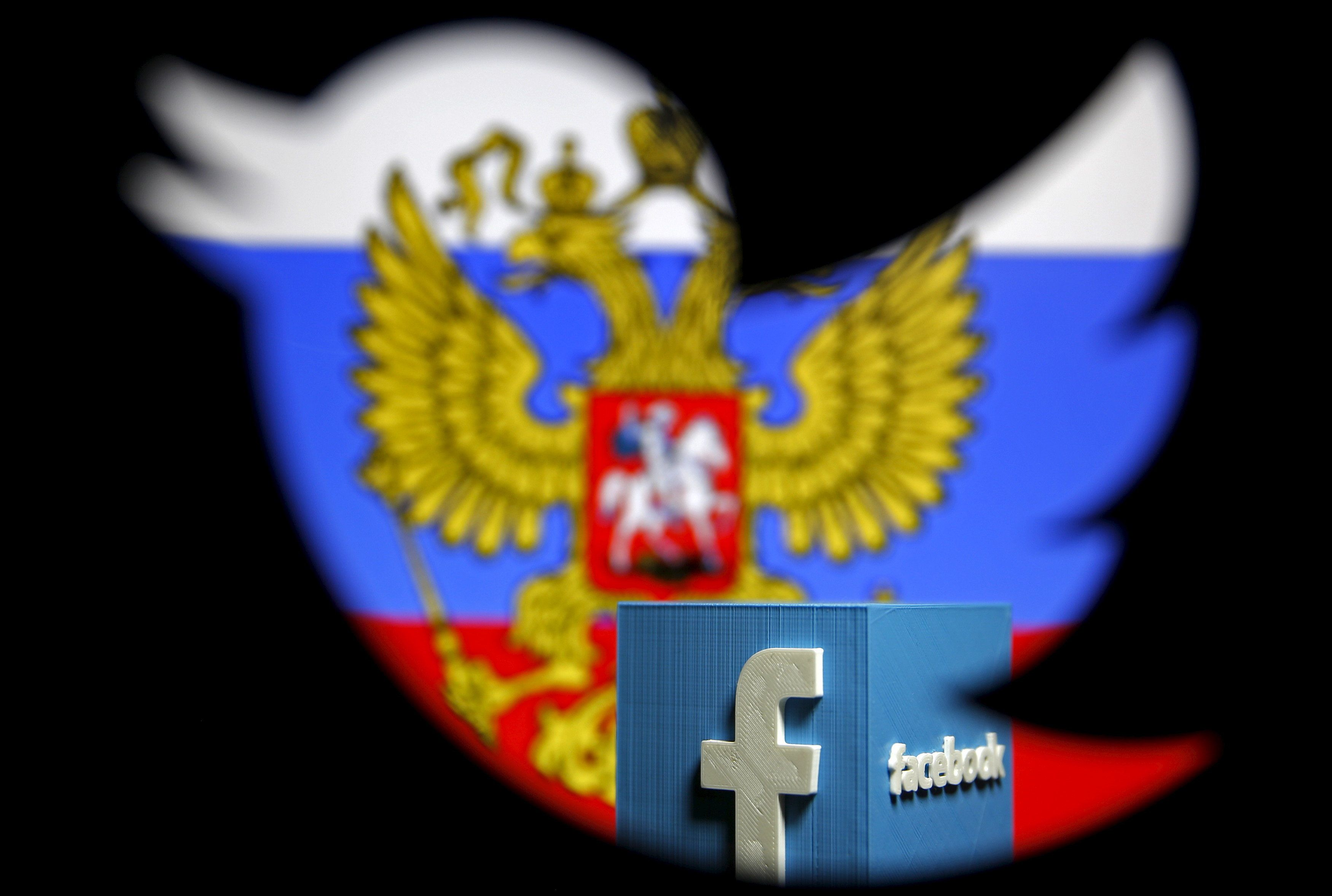 A Russian flag and a model of the Facebook logo are seen through a cutout of the Twitter logo in this photo illustration