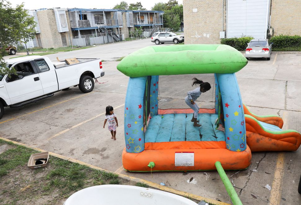 Monica Cruz, 7, jumps in an inflatable bouncy house as her neighbor Ashley Guerrero Monterrosa, 2, walks in the parking lot a