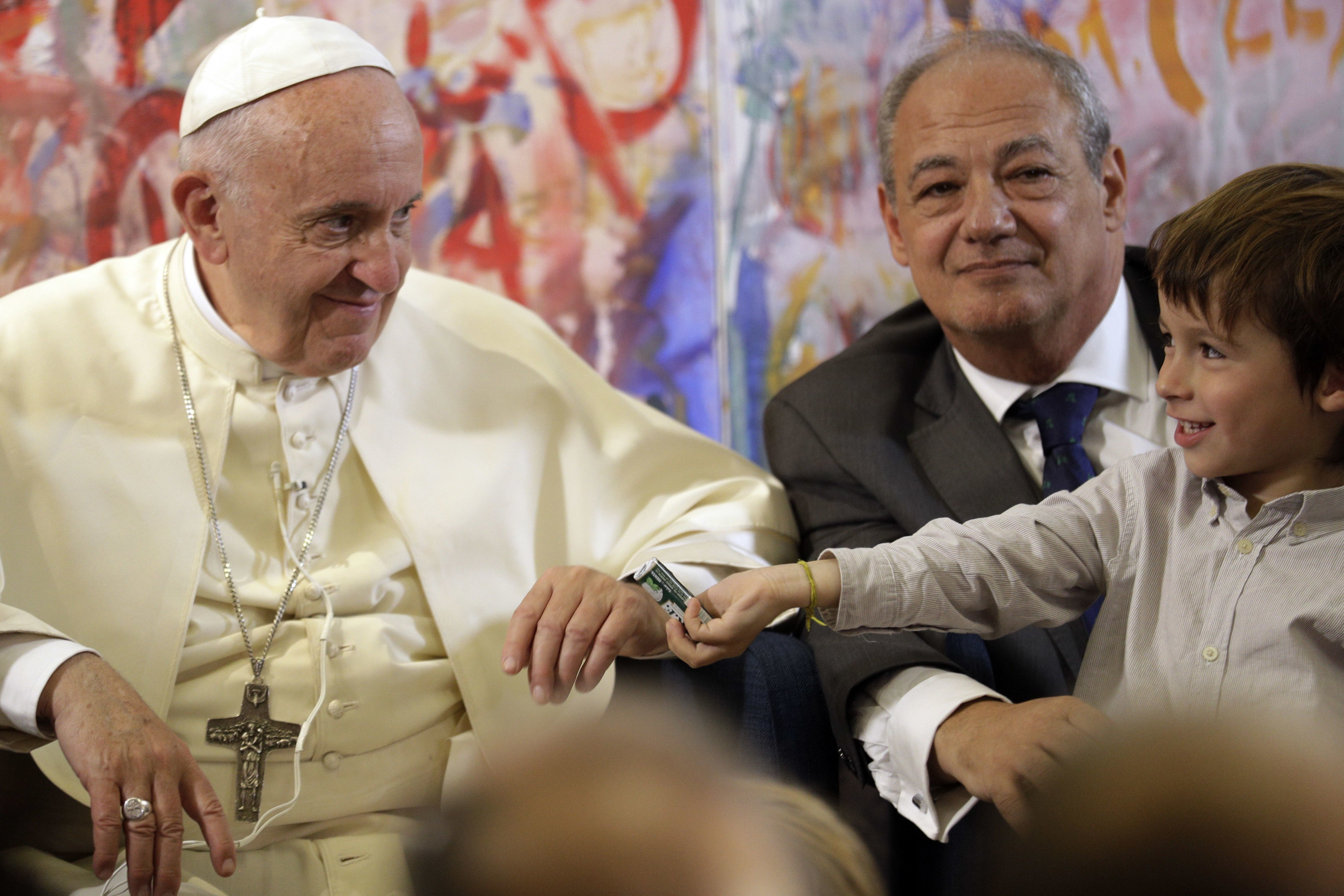 Pope Francis (L) looks at a child as he attends a meeting with members of the Scholas Occurrentes initiative, in Palazzo San