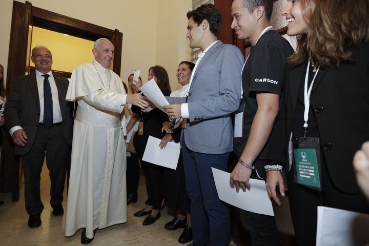Pope Francis (C) greets people as he attends a meeting with members of the Scholas Occurrentes initiative, in Palazzo San Cal