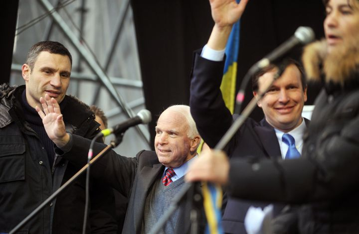 Senators John McCain and Chris Murphy wave to protestors as Ukrainian UDAR party leader Vitali Klitschko looks on during a ma
